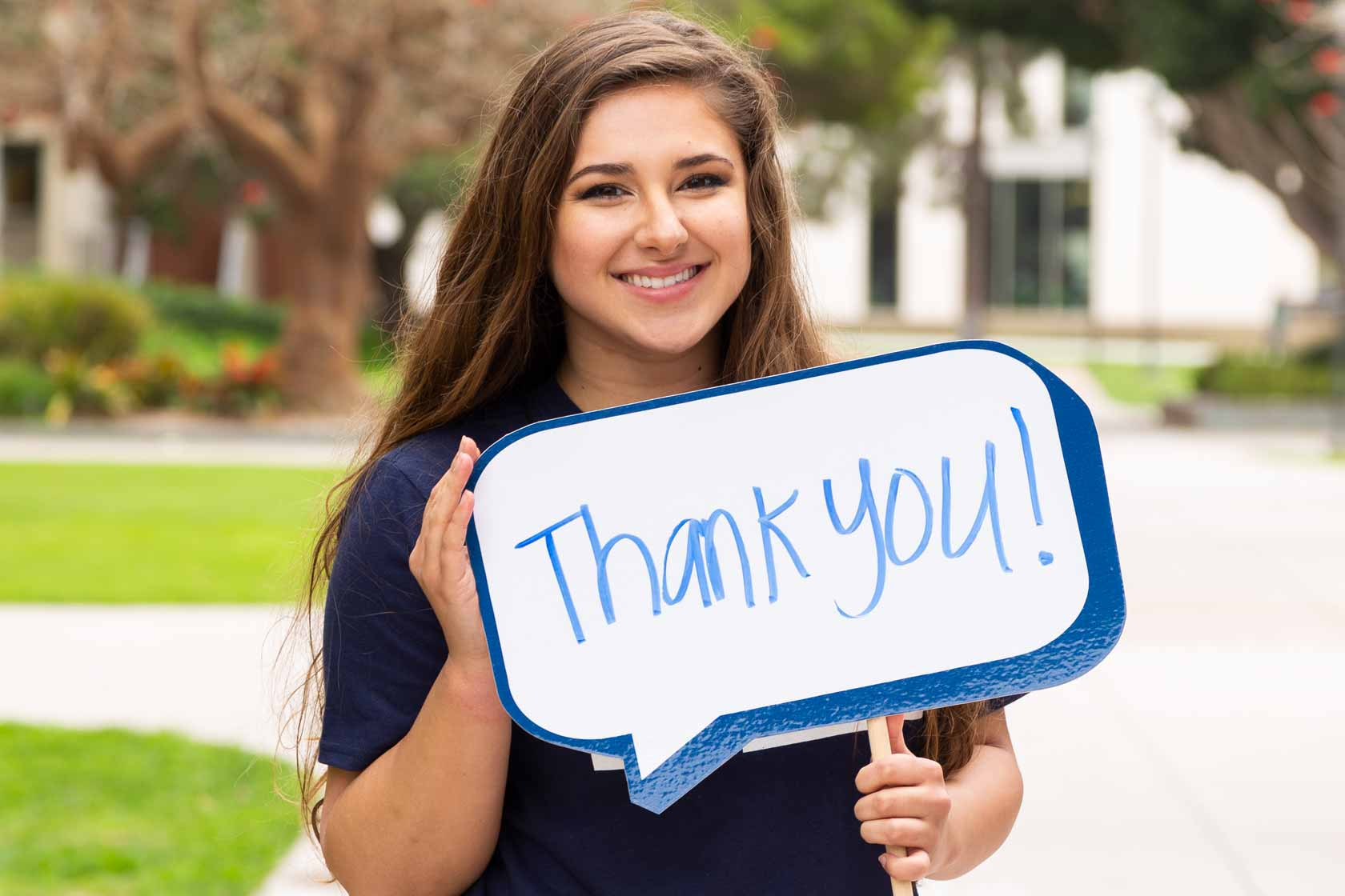 Student with thank you sign
